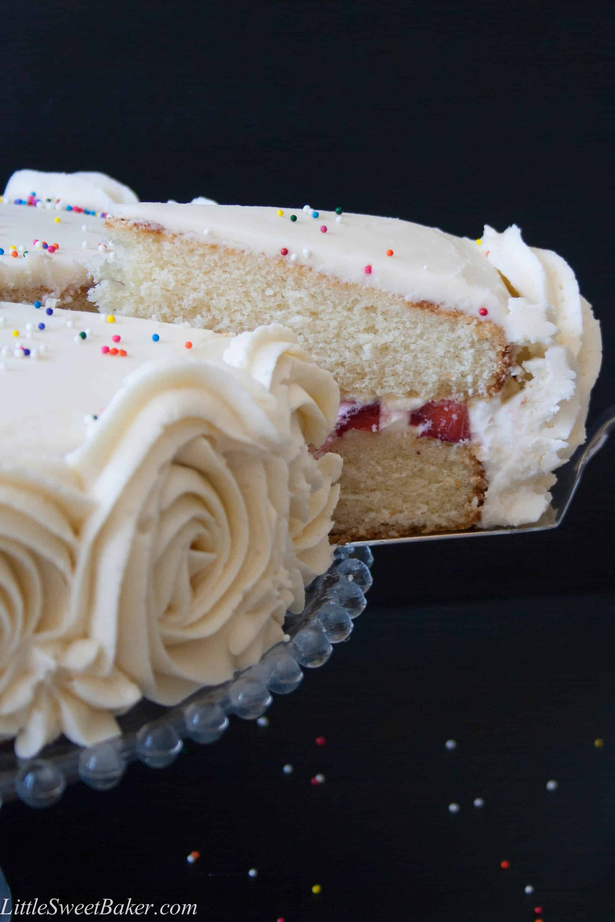 Moist and fluffy vanilla cake with strawberries and cream filling, surrounded with vanilla buttercream.